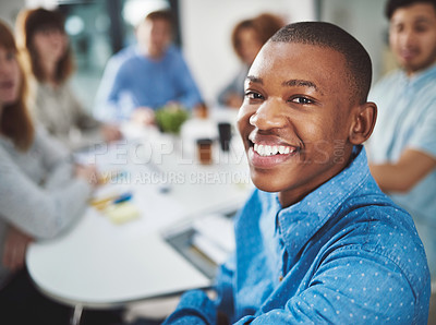 Buy stock photo Cropped portrait of a young businessman looking over his shoulder while sitting in a boardroom with his colleagues