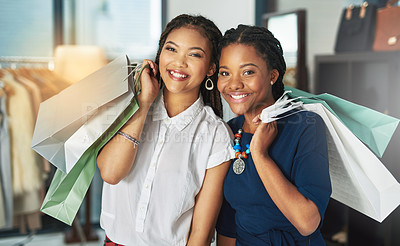 Buy stock photo Cropped shot of two women smiling and holding shopping bags in a store
