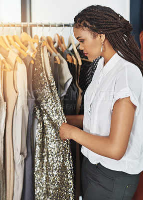 Buy stock photo Cropped shot of a young woman taking a sparkly dress off a rail in a clothing store