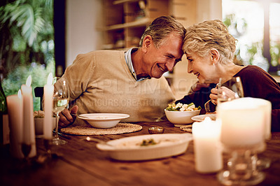 Buy stock photo Shot of an elderly couple enjoying a meal and wine together at home