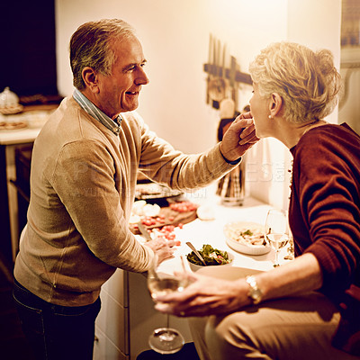 Buy stock photo Shot of an elderly man giving his wife something to taste while he cooks in the kitchen