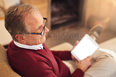 Buy stock photo Shot of a senior man using his digital tablet while sitting on a sofa