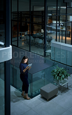 Buy stock photo Shot of a young businesswoman working late on a digital tablet in a modern office