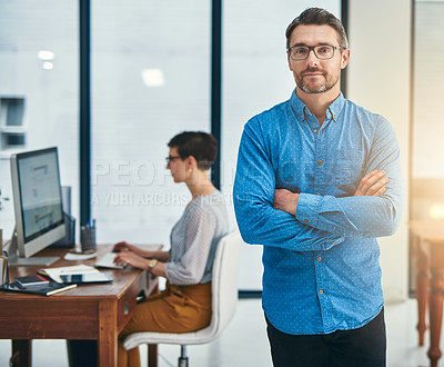 Buy stock photo Portrait of a mature businessman standing in an office with a colleague in the background