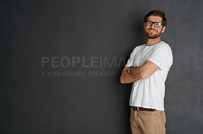 Buy stock photo Studio portrait of a young man standing with his arms folded against a grey background