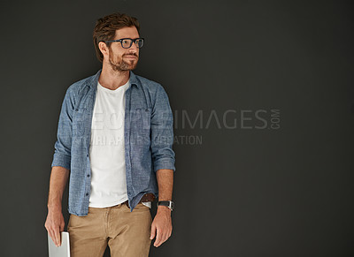 Buy stock photo Studio shot of a young man holding his tablet against a grey background