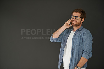 Buy stock photo Studio portrait of a young man talking on his cellphone against a grey background