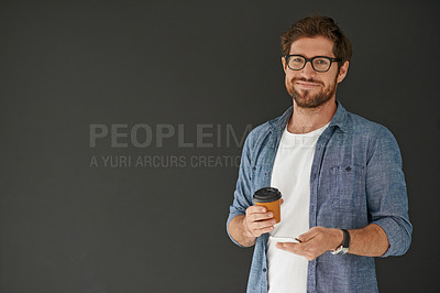Buy stock photo Studio portrait of a young man drinking coffee and sending a text against a grey background