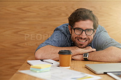 Buy stock photo Cropped portrait of a young man resting his head on his hands while sitting at a table