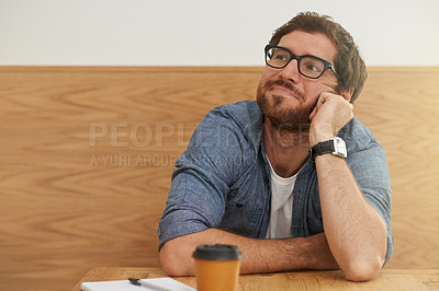 Buy stock photo Cropped shot of a young man resting his head on his hand while sitting at a table