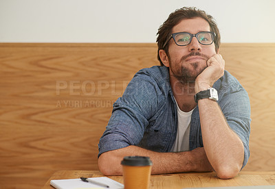 Buy stock photo Cropped portrait of a young man resting his head on his hand while sitting at a table