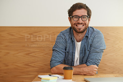 Buy stock photo Cropped portrait of a young man smiling broadly at the camera while sitting at a table