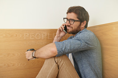 Buy stock photo Cropped shot of a young man talking on his cellphone while sitting at a table