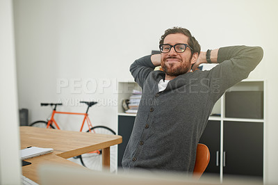 Buy stock photo Portrait of a young entrepreneur relaxing at his work desk