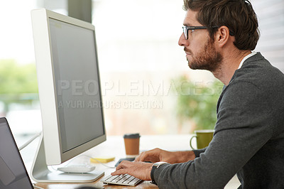 Buy stock photo Shot of a young entrepreneur using a computer at his work desk