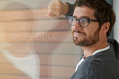 Buy stock photo Portrait of a confident young entrepreneur leaning against a glass window in his office