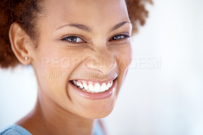 Buy stock photo Closeup portrait of a smart young female smiling and looking against light background