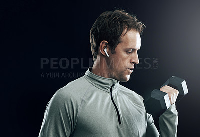 Buy stock photo Studio shot of a fit man listening to music on wireless earphones while lifting weights against a black background