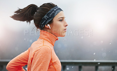 Buy stock photo Shot of a fit young woman using wireless earphones during her workout on a rainy day outside