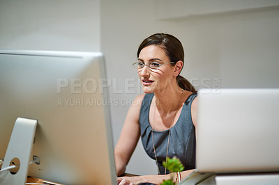 Buy stock photo Shot of a professional businesswoman using a computer at her office desk