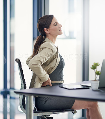 Buy stock photo Shot of a businesswoman suffering from back pain at her office desk