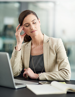 Buy stock photo Shot of a businesswoman suffering from a headache at her office desk