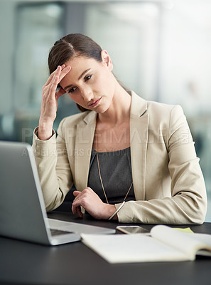 Buy stock photo Shot of a businesswoman looking stressed out at her office desk