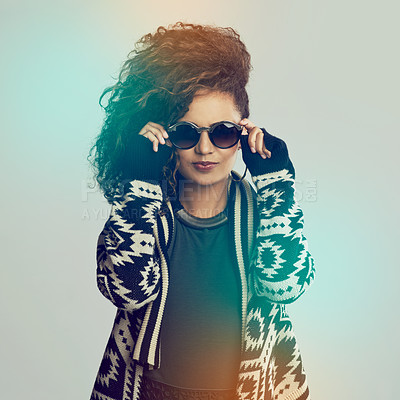 Buy stock photo Cropped shot of a fashionable young woman wearing shades while posing in the studio