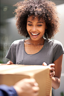 Buy stock photo Shot of a young woman looking excited about receiving her package