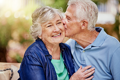 Buy stock photo Cropped shot of an affectionate senior couple sitting in their backyard