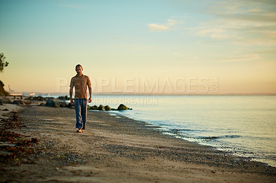 Buy stock photo Shot of a man going for a walk along the water's edge at the beach