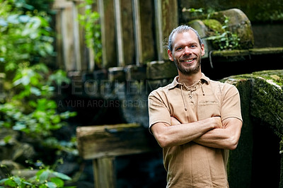 Buy stock photo Portrait of a handsome man standing with his arms folded outdoors