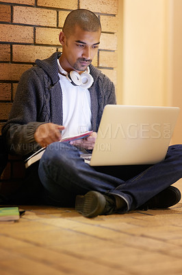Buy stock photo Shot of a college student using his laptop while sitting in a hallway at campus