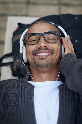 Buy stock photo Cropped shot of a college student listening to music on headphones at campus