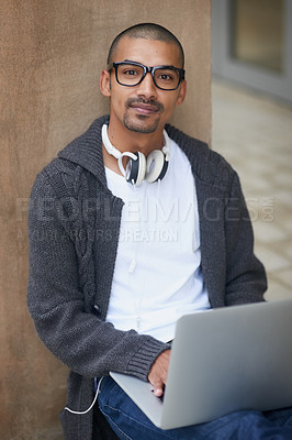 Buy stock photo Portrait of a college student using his laptop while sitting outside at campus