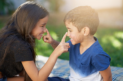 Buy stock photo Shot of a young brother and sister touching each other's noses while playing outside their home