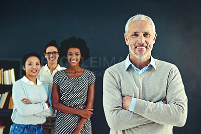 Buy stock photo Studio portrait of a mature businessman posing with his colleagues in the background