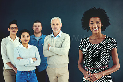 Buy stock photo Studio portrait of an attractive young businesswoman posing with his colleagues in the background