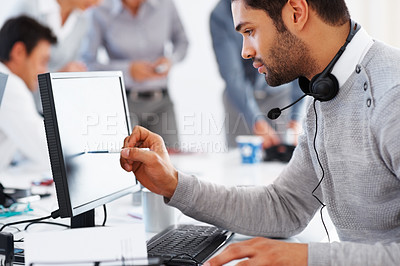 Buy stock photo Male customer executive using computer with colleagues discussing in background
