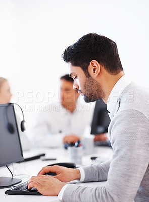 Buy stock photo Business man busy working on computer with colleagues in background