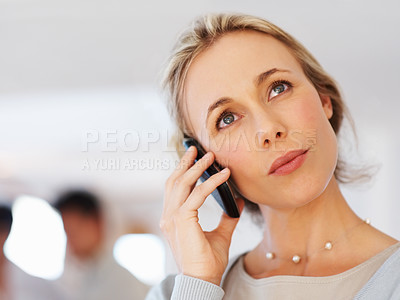 Buy stock photo Closeup of middle aged business woman using cellphone with colleagues in background