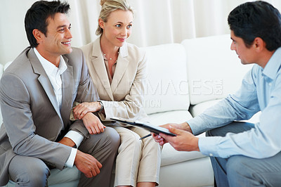 Buy stock photo Happy couple discussing financial matter with male advisor