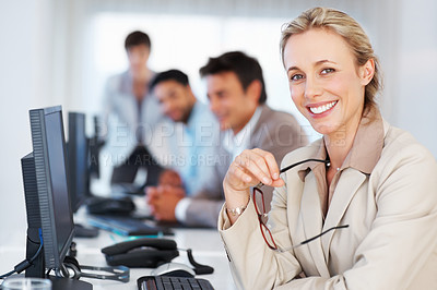 Buy stock photo Business woman at work giving you an attractive smile with colleagues in background