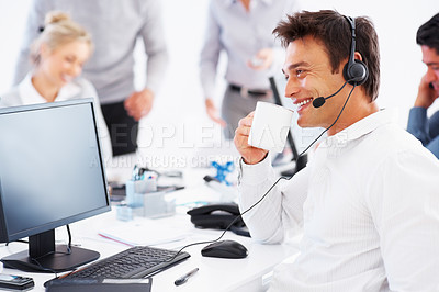 Buy stock photo Male customer service representative talking on headset while drinking coffee with colleagues in background