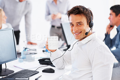 Buy stock photo Smiling call center operator holding coffee cup with colleagues in background