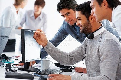 Buy stock photo Business people discussing project on computer with colleagues in background