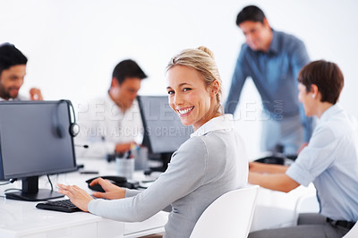 Buy stock photo Smiling business woman working on computer with colleagues in background