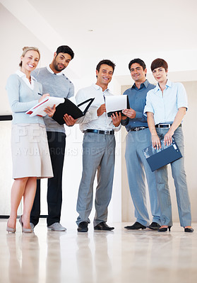 Buy stock photo Full length of corporate executives reviewing business plan in the corridor