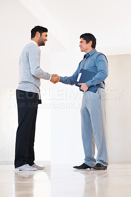 Buy stock photo Full length of business men shaking hands in corridor