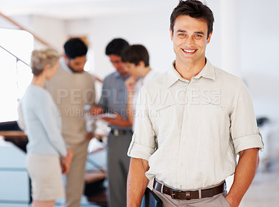 Buy stock photo Portrait of handsome business man smiling with colleagues discussing in background